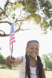 Little girl sitting on grass waving american flag Stock Images