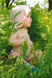 Little girl sitting in a green grass Royalty Free Stock Photos