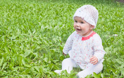 A little girl sitting on green grass Stock Image