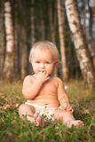 A little girl sitting on green grass Stock Photography