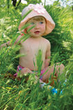 Little girl sitting in a green grass Stock Images