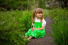 Little girl sitting on green grass in garden in summer day. Little girl sitting on green grass in garden in sunny summer day stock photo