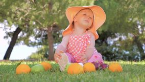 Little princess playing with fruits outdoor. Child in panama having fun outdoor on back yard. Happy childhood concept. Little girl sitting on green grass with stock video