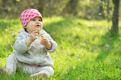 Little girl sitting in green grass Royalty Free Stock Images