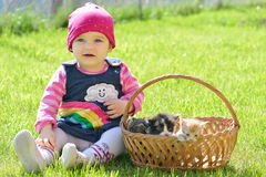 Little girl sitting in green grass with three kittens in basket Royalty Free Stock Photos