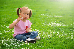 Little girl is sitting on green meadow Royalty Free Stock Image