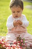 Little girl is sitting on green meadow and play with flowers Royalty Free Stock Images