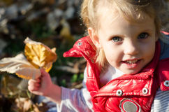 Little girl sitting on the ground with autumn leaves in her hand Royalty Free Stock Photo