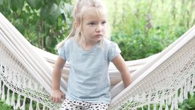 Little girl sitting on a hammock in the summer on a farm stock video