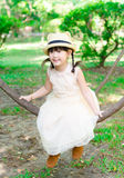 Little girl sitting and hanging on the tree portrait Stock Photography