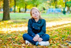 Little girl sitting having fun in an autumn park stock image