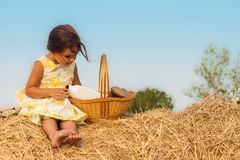 Little girl sitting on haystack with a basket of healthy food Stock Photos