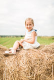 Little girl is sitting on a haystack, a summer concept royalty free stock images