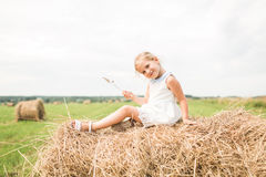 Little girl is sitting on a haystack, a summer concept stock photo