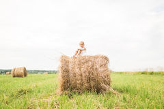 Little girl is sitting on a haystack, a summer concept stock photos