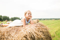 Little girl is sitting on a haystack, a summer concept royalty free stock image