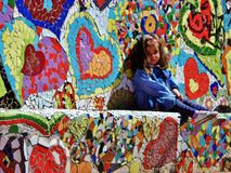 Little Girl Sitting on a Heart Mosaic Bench in a Park Stock Images