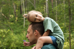 Little girl sitting on her father's shoulders Stock Photography
