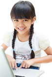 Little girl is sitting with her laptop Stock Photos