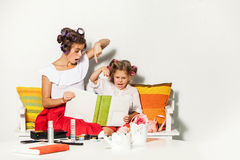 Little girl sitting with her mother and looking at a photo album Stock Photography