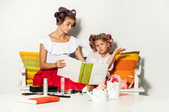 Little girl sitting with her mother and looking at a photo album Royalty Free Stock Photography