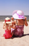 Little girl sitting with her mother on the shore of the sea Royalty Free Stock Photography