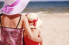 Little girl sitting with her mother on the shore of the sea Stock Image