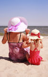 Little girl sitting with her mother on the shore of the sea Royalty Free Stock Photos
