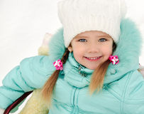 Little girl sitting on her sledge in winter day Royalty Free Stock Photo