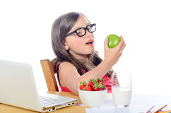 A little girl sitting at his desk eating an apple Stock Photos