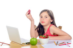 A little girl sitting at his desk eating a strawberry Stock Image