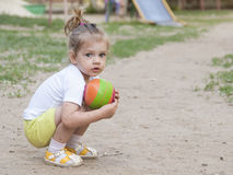 Little girl sitting on his haunches with a ball on the Playground Royalty Free Stock Photography