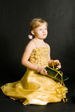 Little girl sitting and holding pr Royalty Free Stock Images