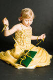 Little girl sitting and holding pr Royalty Free Stock Photo