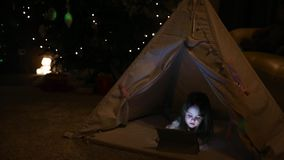Little girl sitting at home in a tent against the background of a Christmas tree playing games on an electronic tablet stock video