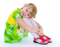 Little girl sitting hugging her knees and smiling Royalty Free Stock Image
