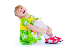Little girl sitting hugging her knees and smiling cheerfully. Stock Photo