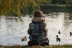 A little girl sitting on a lake side, looking at the water and feeding ducks Royalty Free Stock Photography