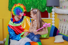 Little girl sitting on the lap of a cheerful clown Royalty Free Stock Photo