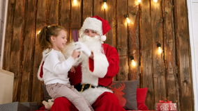 Little girl sitting on the lap of old Santa and brushing his beard stock video footage
