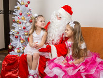Little girl sitting on lap of Santa Claus and tells poem Royalty Free Stock Photography