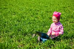 Little girl sitting with a laptop Stock Photography