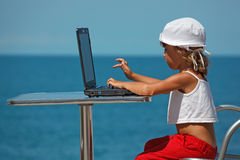 Little girl sitting at laptop at background of sea Royalty Free Stock Image