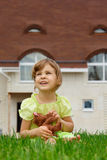 Little girl sitting on lawn in front of new home Royalty Free Stock Photography