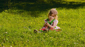 Little girl sitting on the lawn lit by sun. Little girl age of three years, sitting on the lawn lit by the sun and holding a dandelion Stock Image