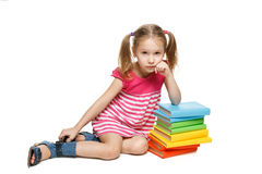Little girl sitting leaning on the stack of books Stock Images