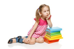 Little girl sitting leaning on the stack of books Royalty Free Stock Photo