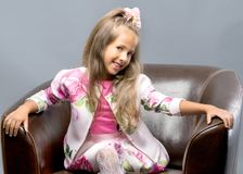 A little girl is sitting on a leather chair. A nice little girl is sitting on a leather chair. The concept of family happiness and home comfort Stock Photo
