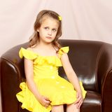 A little girl is sitting on a leather chair. A nice little girl is sitting on a leather chair. The concept of family happiness and home comfort Royalty Free Stock Image