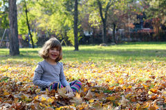 Little girl sitting on leaves in autumn park Royalty Free Stock Images